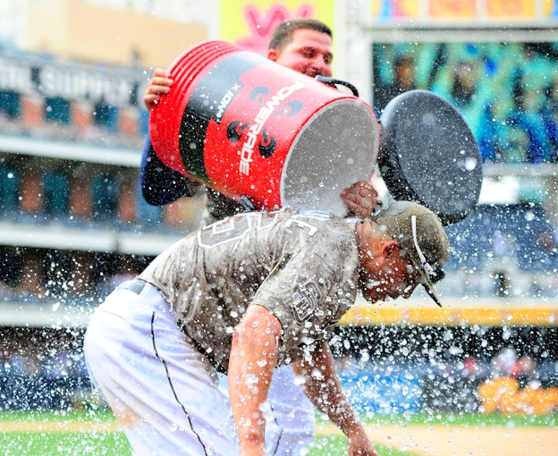 Aug 18, 2013; San Diego, CA, USA; San Diego Padres center fielder Will Venable (25) is dumped with water by first baseman Yonder Alonso (23) after hitting a walk-off home run in the ninth inning to beat the New York Mets 4-3 at Petco Park. Mandatory Credit: Christopher Hanewinckel-USA TODAY Sports