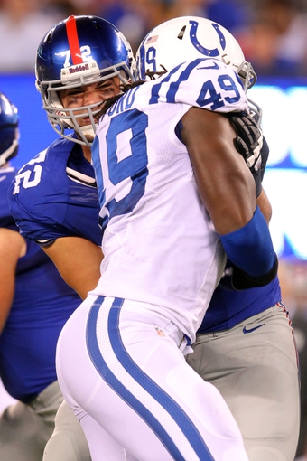 Aug 18, 2013; East Rutherford, NJ, USA; New York Giants offensive tackle Justin Pugh (72) blocks Indianapolis Colts linebacker Caesar Rayford (49) during the third quarter of a preseason game at MetLife Stadium. Mandatory Credit: Brad Penner-USA TODAY Sports