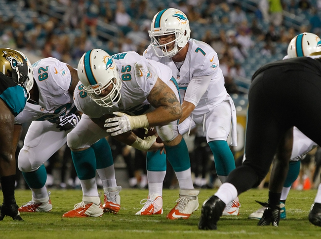 Aug 9, 2013; Jacksonville, FL, USA; Miami Dolphins quarterback Pat Devlin (7) gets the ball hiked by center Sam Brenner (65) during the second half against the Jacksonville Jaguars at EverBank Field. Miami Dolphins defeated the Jacksonville Jaguars 27-3. Mandatory Credit: Kim Klement-USA TODAY Sports