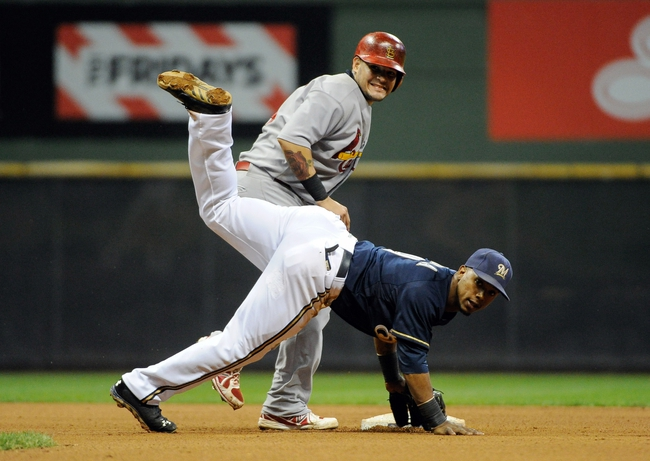 Aug 19, 2013; Milwaukee, WI, USA;  Milwaukee Brewers shortstop Jean Segura (front) turns a double play after forcing out St. Louis Cardinals catcher Yadier Molina (back) in the 8th inning at Miller Park. Mandatory Credit: Benny Sieu-USA TODAY Sports