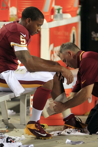 Aug 19, 2013; Landover, MD, USA; Washington Redskins quarterback Pat White (5) has his leg taped by a team trainer on the sidelines against the Pittsburgh Steelers in the fourth quarter at FedEx Field. The Redskins won 24-13. Mandatory Credit: Geoff Burke-USA TODAY Sports