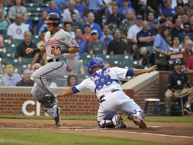 Aug 20, 2013; Chicago, IL, USA; Washington Nationals shortstop Ian Desmond (20) scores as Chicago Cubs catcher Welington Castillo (53) makes a tag during the first inning at Wrigley Field. Mandatory Credit: David Banks-USA TODAY Sports