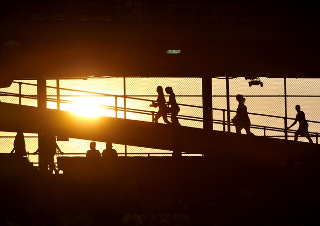 Aug 20, 2013; Chicago, IL, USA; People walk in the stands as the sun sets during a ballgame between the Chicago Cubs and the Washington Nationals at Wrigley Field. Mandatory Credit: David Banks-USA TODAY Sports