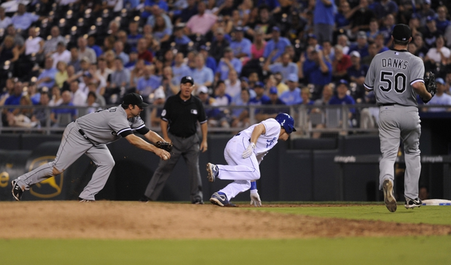 Aug 20, 2013; Kansas City, MO, USA; Kansas City Royals second baseman Chris Getz (17) is tagged out by Chicago White Sox first baseman Paul Konerko (14) after being picked off by pitcher John Danks (50) in the eighth inning at Kauffman Stadium. Chicago won the game 2-0. Mandatory Credit: John Rieger-USA TODAY Sports