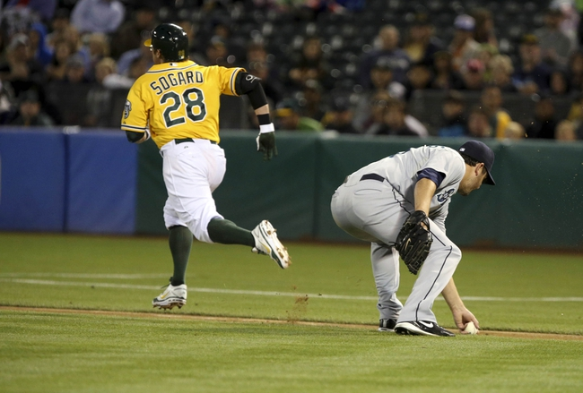 Aug 20, 2013; Oakland, CA, USA; Seattle Mariners starting pitcher Joe Saunders (23) gathers the ball as Oakland Athletics shortstop Eric Sogard (28) reaches first base on a bunt during the fourth inning at O.co Coliseum. Mandatory Credit: Kelley L Cox-USA TODAY Sports