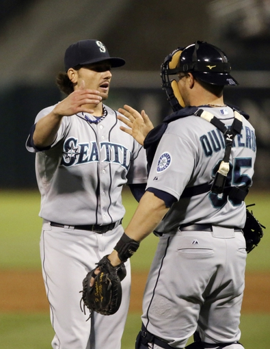 Aug 20, 2013; Oakland, CA, USA; Seattle Mariners relief pitcher Danny Farquhar (40) celebrates with catcher Humberto Quintero (35) after the win against the Oakland Athletics at O.co Coliseum. The Seattle Mariners defeated the Oakland Athletics 7-4. Mandatory Credit: Kelley L Cox-USA TODAY Sports