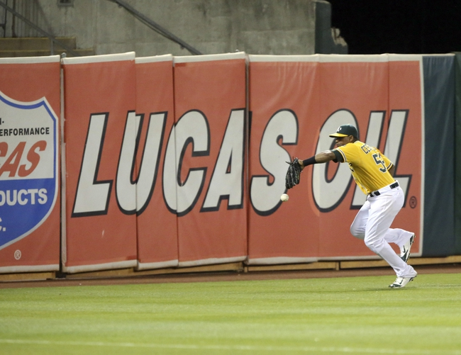 Aug 20, 2013; Oakland, CA, USA; Oakland Athletics left fielder Yoenis Cespedes (52) is unable to control the ball against the Seattle Mariners during the eighth inning at O.co Coliseum. The Seattle Mariners defeated the Oakland Athletics 7-4. Mandatory Credit: Kelley L Cox-USA TODAY Sports