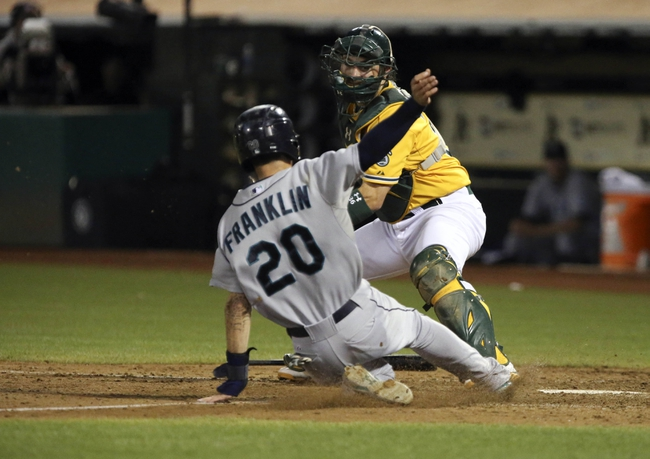 Aug 20, 2013; Oakland, CA, USA; Seattle Mariners second baseman Nick Franklin (20) slides safely home against Oakland Athletics catcher Derek Norris (36) during the eighth inning at O.co Coliseum. The Seattle Mariners defeated the Oakland Athletics 7-4. Mandatory Credit: Kelley L Cox-USA TODAY Sports