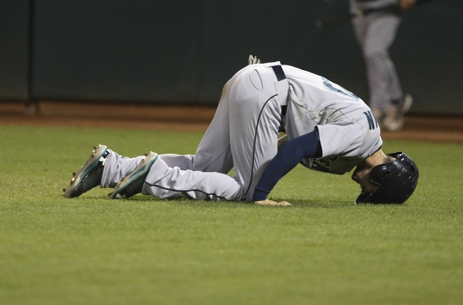 Aug 20, 2013; Oakland, CA, USA; Seattle Mariners second baseman Nick Franklin (20) down with an injury after sliding home for a run against the Oakland Athletics during the eighth inning at O.co Coliseum. The Seattle Mariners defeated the Oakland Athletics 7-4. Mandatory Credit: Kelley L Cox-USA TODAY Sports