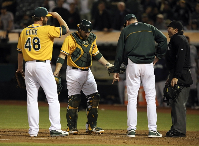 Aug 20, 2013; Oakland, CA, USA; Oakland Athletics relief pitcher Ryan Cook (48), catcher Derek Norris (36), and manager Bob Melvin (6) speak with home plate umpire Paul Schrieber (43) after a against the Seattle Mariners run during the eighth inning at O.co Coliseum. The Seattle Mariners defeated the Oakland Athletics 7-4. Mandatory Credit: Kelley L Cox-USA TODAY Sports