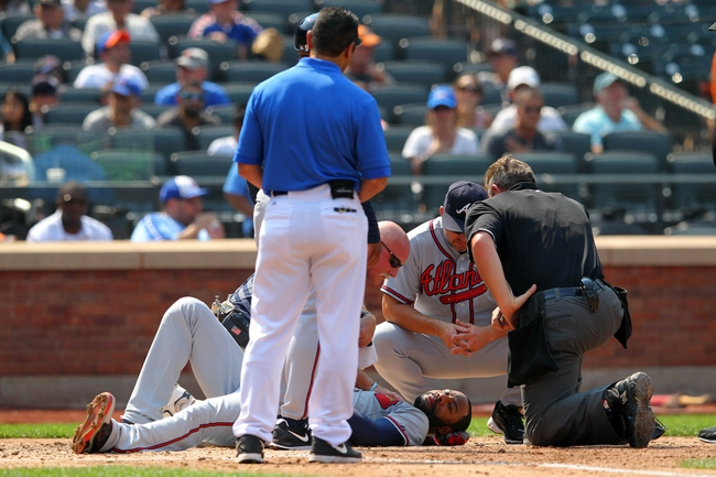 Aug 21, 2013; New York, NY, USA; Atlanta Braves right fielder Jason Heyward (22) is tended to by trainers and Fredi Gonzalez (33) and home plate umpire Greg Gibson (53) after getting hit in the face by a pitch from New York Mets starting pitcher Jonathon Niese (not pictured) during the sixth inning of a game at Citi Field. Mandatory Credit: Brad Penner-USA TODAY Sports