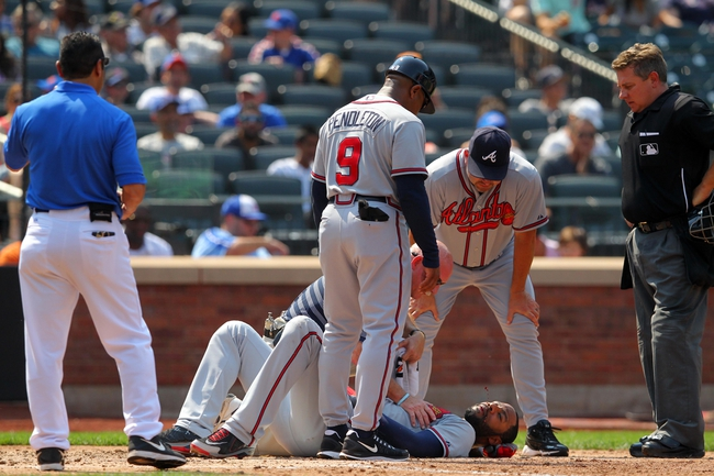Aug 21, 2013; New York, NY, USA; Atlanta Braves right fielder Jason Heyward (22) spits blood as he is tended to by trainers and Fredi Gonzalez (33) and home plate umpire Greg Gibson (53) after getting hit in the face by a pitch from New York Mets starting pitcher Jonathon Niese (not pictured) during the sixth inning of a game at Citi Field. Mandatory Credit: Brad Penner-USA TODAY Sports