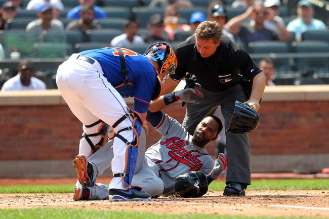 Aug 21, 2013; New York, NY, USA; Atlanta Braves right fielder Jason Heyward (22) is hit in the face by a pitch from New York Mets starting pitcher Jonathon Niese (not pictured) and is tended to by Mets catcher John Buck (44) and home plate umpire Greg Gibson (53) during the sixth inning of a game at Citi Field. Mandatory Credit: Brad Penner-USA TODAY Sports
