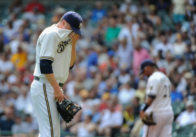Aug 21, 2013; Milwaukee, WI, USA;  Milwaukee Brewers pitcher Tom Gorzelanny (left) reacts after giving up a solo homer to St. Louis Cardinals first baseman Allen Craig (not pictured) in the 2nd inning at Miller Park. Mandatory Credit: Benny Sieu-USA TODAY Sports