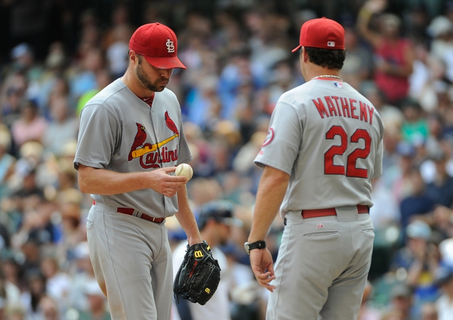 Aug 21, 2013; Milwaukee, WI, USA; St. Louis Cardinals pitcher Jake Westbrook (left) hands the ball over to manager Mike Matheny (right) in the 5th inning during the game against the Milwaukee Brewers at Miller Park. Mandatory Credit: Benny Sieu-USA TODAY Sports