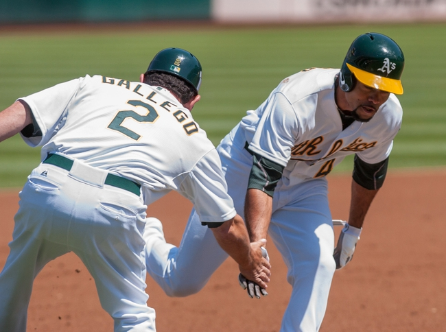 Aug 21, 2013; Oakland, CA, USA; Oakland Athletics third base coach Mike Gallego (2) congratulates center fielder Coco Crisp (4) after he hit a home run against the Seattle Mariners during the first inning at O.Co Coliseum. Mandatory Credit: Ed Szczepanski-USA TODAY Sports