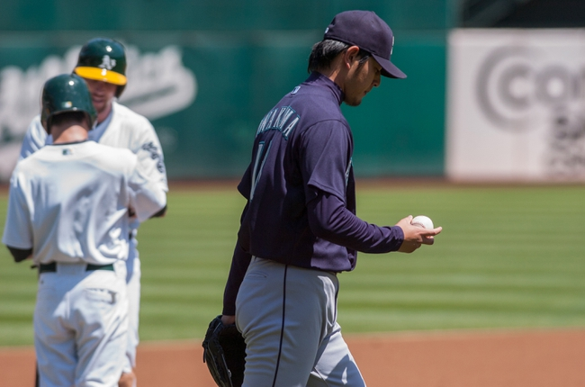 Aug 21, 2013; Oakland, CA, USA; Seattle Mariners starting pitcher Hisashi Iwakuma (18) evaluates the baseball after giving up a triple to Oakland Athletics shortstop Jed Lowrie (8) during the first inning at O.Co Coliseum. Mandatory Credit: Ed Szczepanski-USA TODAY Sports