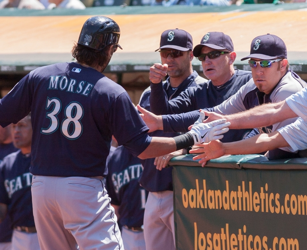 Aug 21, 2013; Oakland, CA, USA; Seattle Mariners right fielder Michael Morse (38) is congratulated by his teammates after hitting a home run against the Oakland Athletics during the second inning at O.Co Coliseum. Mandatory Credit: Ed Szczepanski-USA TODAY Sports