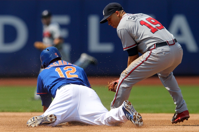 Aug 21, 2013; New York, NY, USA; New York Mets center fielder Juan Lagares (12) slides safely into second with a double in front of Atlanta Braves shortstop Andrelton Simmons (19) during the fifth inning of a game at Citi Field. Mandatory Credit: Brad Penner-USA TODAY Sports
