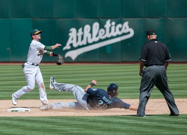 Aug 21, 2013; Oakland, CA, USA; Oakland Athletics shortstop Jed Lowrie (8) attempts to turn a double play against Seattle Mariners right fielder Michael Morse (38) during the eighth inning at O.Co Coliseum. The Seattle Mariners defeated the Oakland Athletics 5-3. Mandatory Credit: Ed Szczepanski-USA TODAY Sports