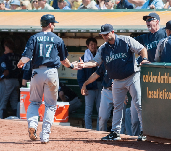 Aug 21, 2013; Oakland, CA, USA; Seattle Mariners first baseman Justin Smoak (17) is congratulated by the Seattle Mariners coaching staff after scoring against the Oakland Athletics during the eighth inning at O.Co Coliseum. The Seattle Mariners defeated the Oakland Athletics 5-3. Mandatory Credit: Ed Szczepanski-USA TODAY Sports
