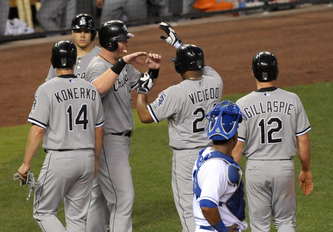 Aug 21, 2013; Kansas City, MO, USA; Chicago White Sox left fielder Dayan Viciedo (24) is congratulated by first baseman Adam Dunn (32) after hitting a grand slam home run in the fourth inning of the game against the Kansas City Royals at Kauffman Stadium. Mandatory Credit: Denny Medley-USA TODAY Sports