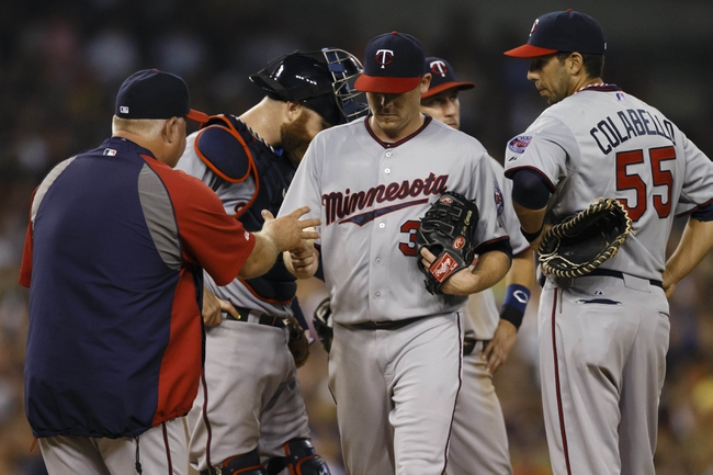Aug 21, 2013; Detroit, MI, USA; Minnesota Twins manager Ron Gardenhire (35) takes the ball to relieve starting pitcher Kevin Correia (30) in the seventh inning against the Detroit Tigers at Comerica Park. Mandatory Credit: Rick Osentoski-USA TODAY Sports