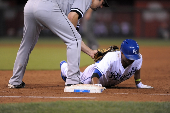 Aug 21, 2013; Kansas City, MO, USA; Kansas City Royals shortstop Alcides Escobar (2) is safe at first base as Chicago White Sox designated hitter Paul Konerko (14) cannot make the tag in the fifth inning at Kauffman Stadium. Mandatory Credit: Denny Medley-USA TODAY Sports