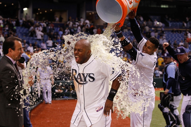 Aug 14, 2013; St. Petersburg, FL, USA; Tampa Bay Rays left fielder Jason Bourgeois (13) gets a gatorade bath by teammate shortstop Yunel Escobar (11) as he gets interviewed by Sunsports announcer Todd Kalas after he hit the game winning RBI single against the Seattle Mariners at Tropicana Field. Tampa Bay Rays defeated the Seattle Mariners 5-4. Mandatory Credit: Kim Klement-USA TODAY Sports