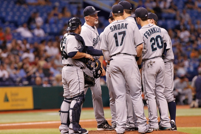 Aug 14, 2013; St. Petersburg, FL, USA; Seattle Mariners pitching coach Carl Willis (48) comes out to talk with starting pitcher Aaron Harang (39) and infielders on the mound against the Tampa Bay Rays at Tropicana Field. Tampa Bay Rays defeated the Seattle Mariners 5-4. Mandatory Credit: Kim Klement-USA TODAY Sports