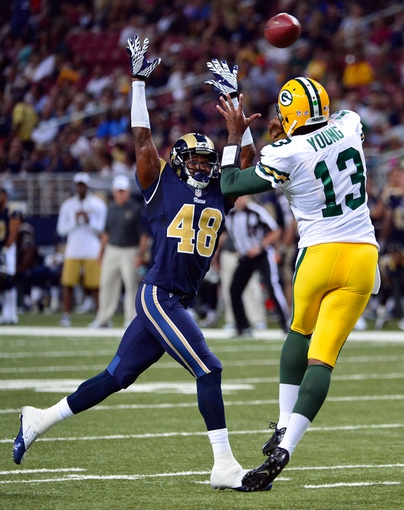 Aug 17, 2013; St. Louis, MO, USA; Green Bay Packers quarterback Vince Young (13) attempts a pass as St. Louis Rams strong safety Rashard Hall (48) pressures at the Edward Jones Dome during the second half. The Packers defeated the Rams 19-7. Mandatory Credit: Scott Rovak-USA TODAY Sports