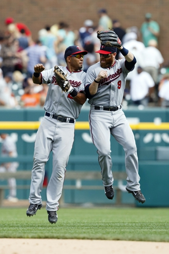 Aug 22, 2013; Detroit, MI, USA; Minnesota Twins left fielder Wilkin Ramirez (22) and right fielder Ryan Doumit (9) celebrate after the game against the Detroit Tigers at Comerica Park. Minnesota won 7-6. Mandatory Credit: Rick Osentoski-USA TODAY Sports