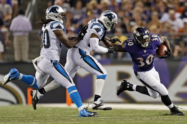 Aug 22, 2013; Baltimore, MD, USA; Baltimore Ravens running back Bernard Pierce (30) runs past Carolina Panthers cornerback Drayton Florence (29) at M&T Bank Stadium. Mandatory Credit: Mitch Stringer-USA TODAY Sports