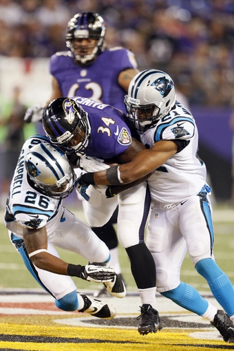 Aug 22, 2013; Baltimore, MD, USA; Baltimore Ravens running back Bobby Rainey (34) is tackled by Carolina Panthers safety D.J. Campbell (26) and safety Mike Mitchell (21) following a gain at M&T Bank Stadium. Mandatory Credit: Mitch Stringer-USA TODAY Sports