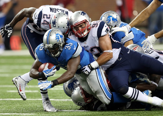 Aug 22, 2013; Detroit, MI, USA; Detroit Lions running back Joique Bell (35) is tackled by New England Patriots defensive end Jake Bequette (92) during 2nd half at Ford Field. Lions won 40-9.  Mandatory Credit: Mike Carter-USA TODAY Sports