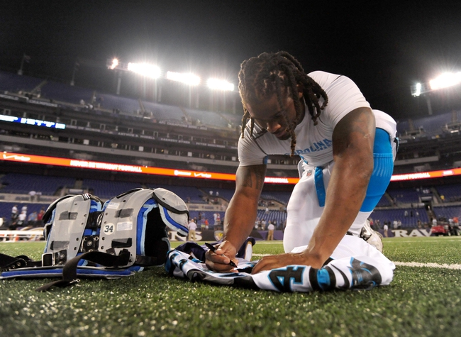 Aug 22, 2013; Baltimore, MD, USA; Carolina Panthers running back DeAngelo Williams (34) signs a jersey for Baltimore Ravens running back Ray Rice (not pictured) at M&T Bank Stadium. Mandatory Credit: Evan Habeeb-USA TODAY Sports