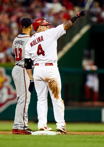 Aug 23, 2013; St. Louis, MO, USA; St. Louis Cardinals catcher Yadier Molina (4) points to his teammates after hitting a double against the Atlanta Braves during the second inning at Busch Stadium. Mandatory Credit: Jeff Curry-USA TODAY Sports