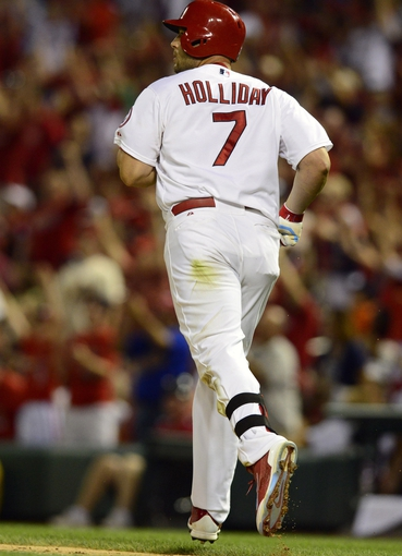 Aug 23, 2013; St. Louis, MO, USA; St. Louis Cardinals left fielder Matt Holliday (7) watches his solo home run off of Atlanta Braves starting pitcher Kris Medlen (not pictured) during the sixth inning at Busch Stadium. Mandatory Credit: Jeff Curry-USA TODAY Sports