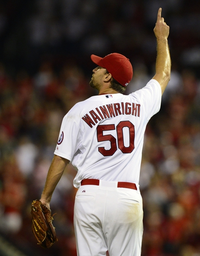 Aug 23, 2013; St. Louis, MO, USA; St. Louis Cardinals starting pitcher Adam Wainwright (50) points to a fly ball hit by Atlanta Braves shortstop Andrelton Simmons (not pictured) to end the game at Busch Stadium. Wainwright threw a complete game defeating the Atlanta 3-1. Mandatory Credit: Jeff Curry-USA TODAY Sports