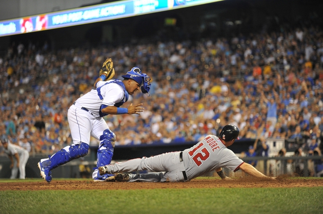 Aug 23, 2013; Kansas City, MO, USA; Kansas City Royals catcher Salvador Perez (13) tags out Washington Nationals base runner Tyler Moore (12) attempting to score a home plate during the seventh inning at Kauffman Stadium.  Mandatory Credit: Peter G. Aiken-USA TODAY Sports
