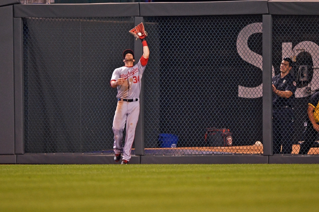 Aug 23, 2013; Kansas City, MO, USA; Washington Nationals right fielder Bryce Harper (34) makes a catch in front of the wall against the Kansas City Royals during the sixth inning at Kauffman Stadium.  Washington beat Kansas City 11-10. Mandatory Credit: Peter G. Aiken-USA TODAY Sports
