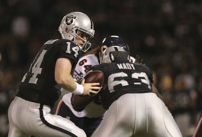 Aug 23, 2013; Oakland, CA, USA; Oakland Raiders quarterback Matthew McGloin (14) looks to hand off the ball against the Chicago Bears during the fourth quarter at O.co Coliseum. The Chicago Bears defeated the Oakland Raiders 34-26. Mandatory Credit: Kelley L Cox-USA TODAY Sports