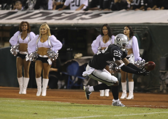 Aug 23, 2013; Oakland, CA, USA; Oakland Raiders cornerback Taiwan Jones (22) bobbles the ball on the kickoff return against the Chicago Bears during the fourth quarter at O.co Coliseum. The Chicago Bears defeated the Oakland Raiders 34-26. Mandatory Credit: Kelley L Cox-USA TODAY Sports