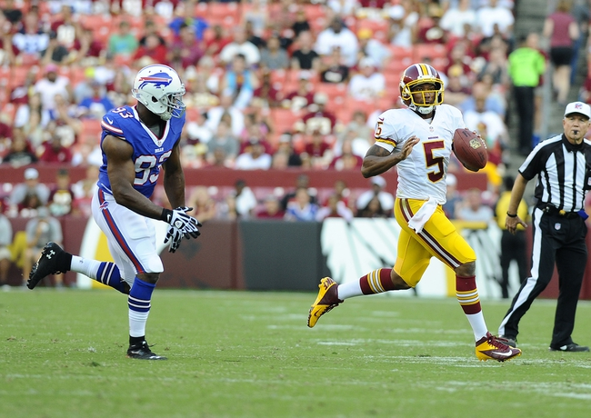 Aug 24, 2013; Landover, MD, USA; Washington Redskins quarterback Pat White (5) rolls out to avoid the rush by Buffalo Bills linebacker Jamaal Westerman (93) during the second half at FedEX Field. Mandatory Credit: Brad Mills-USA TODAY Sports