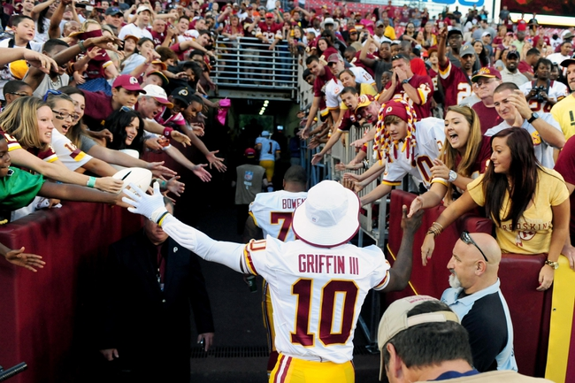 Aug 24, 2013; Landover, MD, USA; Washington Redskins quarterback Robert Griffin III (10) high fives fans after beating the Buffalo Bills 30-7 at FedEx Field. Mandatory Credit: Evan Habeeb-USA TODAY Sports