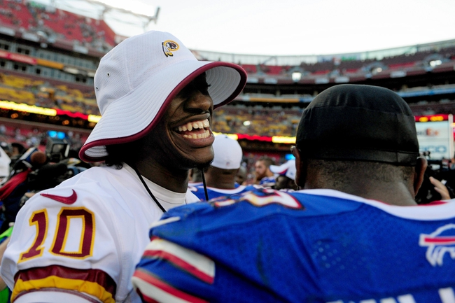 Aug 24, 2013; Landover, MD, USA; Washington Redskins quarterback Robert Griffin III (10) shakes hands with Buffalo Bills safety Aaron Williams (23) after the game at FedEx Field. Mandatory Credit: Evan Habeeb-USA TODAY Sports