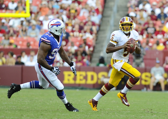 Aug 24, 2013; Landover, MD, USA; Washington Redskins quarterback Pat White (5) rolls out as Buffalo Bills linebacker Jamaal Westerman (93) chases during the second half at FedEX Field. Mandatory Credit: Brad Mills-USA TODAY Sports