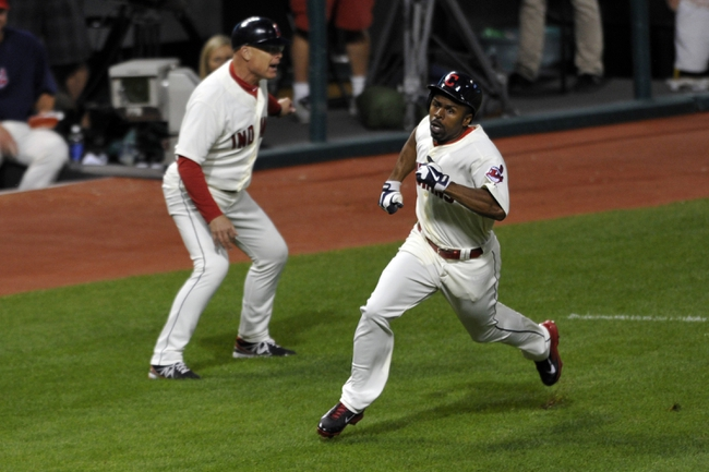 Aug 24, 2013; Cleveland, OH, USA; Cleveland Indians center fielder Michael Bourn (right) passes third base coach Brad Mills while scoring in the fifth inning against the Minnesota Twins at Progressive Field. Mandatory Credit: David Richard-USA TODAY Sports