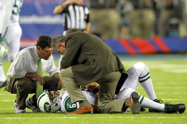 Aug 24, 2013; East Rutherford, NJ, USA; New York Jets quarterback Mark Sanchez (6) is tended to as he lies injured on the field after taking a hit from New York Giants linebacker Mark Herzlich (not pictured) during the fourth quarter of a preseason game at MetLife Stadium. Mandatory Credit: Brad Penner-USA TODAY Sports