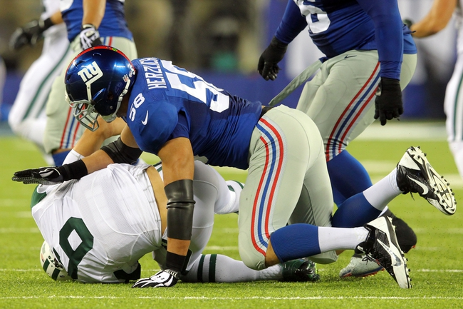 Aug 24, 2013; East Rutherford, NJ, USA; New York Jets quarterback Mark Sanchez (6) is injured after a tackle by New York Giants linebacker Mark Herzlich (58) during the fourth quarter of a preseason game at MetLife Stadium. Mandatory Credit: Brad Penner-USA TODAY Sports